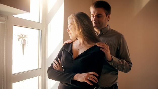 Jeune homme aimant étreignant sa femme en regardant par la fenêtre au coucher du soleil