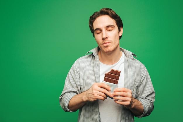 Jeune homme aime manger une barre de chocolat