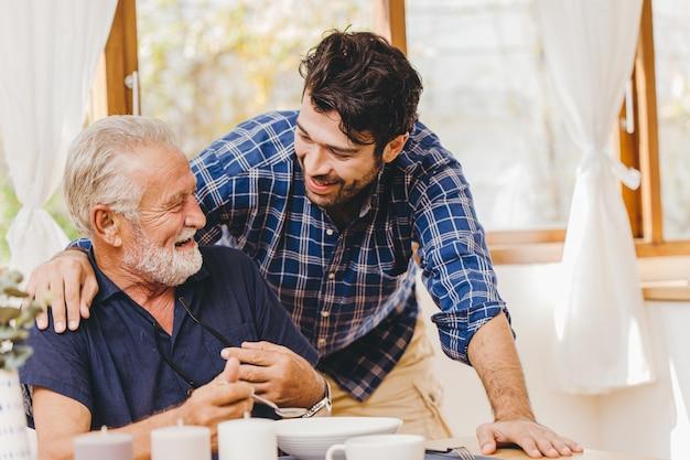 Le jeune homme aime et prend soin d'un aîné qui mange le déjeuner en toute sécurité et reste à la maison, une famille souriante heureuse.