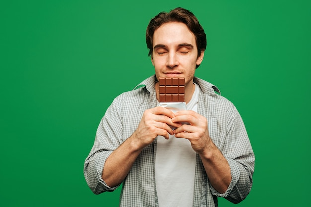 Jeune homme aime sentir la barre de chocolat