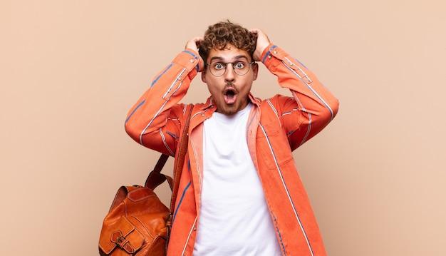 Jeune homme à l'air excité et surpris, bouche bée avec les deux mains sur la tête, se sentant comme un heureux gagnant. concept étudiant