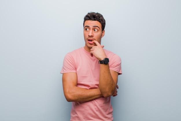 Jeune homme à l'air surpris, nerveux, inquiet ou effrayé, regardant sur le côté vers l'espace copie sur mur gris