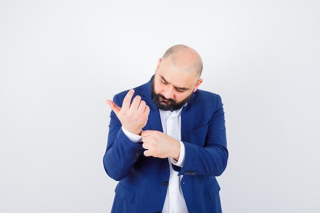 Jeune homme ajustant la manche de sa chemise en chemise blanche, veste et élégant. vue de face.