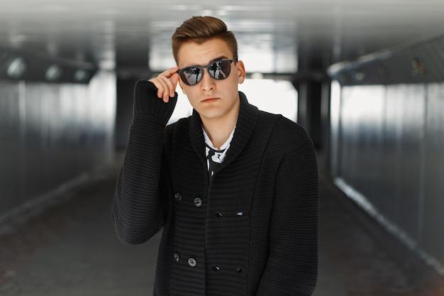 Jeune homme ajuste ses lunettes de soleil