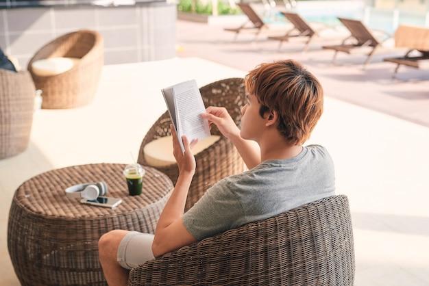 Jeune homme allongé sur la chaise longue et lisant un livre près de la piscine