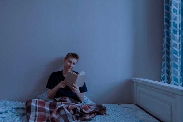 Un jeune homme allongé dans le lit et lit un livre le soir avant d'aller dormir dans la chambre à coucher