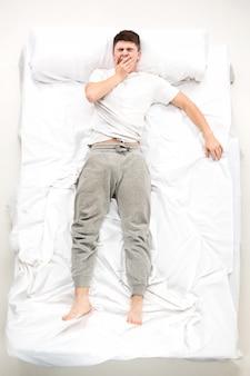 Le jeune homme allongé dans un lit