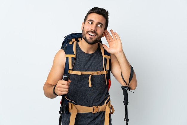 Jeune homme alpiniste avec un gros sac à dos et bâtons de randonnée isolé sur mur blanc en écoutant quelque chose