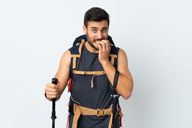 Jeune homme alpiniste avec un gros sac à dos et bâtons de randonnée sur un mur blanc nerveux et effrayé
