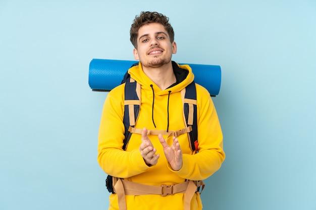 Jeune homme alpiniste avec un gros sac à dos isolé sur le mur bleu applaudissant