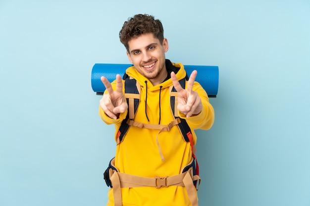 Jeune homme alpiniste avec un gros sac à dos isolé sur mur bleu souriant et montrant le signe de la victoire