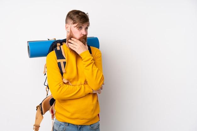 Jeune homme alpiniste avec un gros sac à dos sur un mur blanc isolé en pensant à une idée