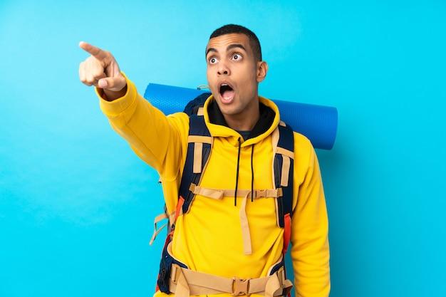 Jeune homme alpiniste avec un gros sac à dos sur un mur bleu isolé loin