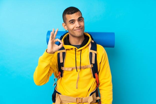 Jeune homme alpiniste avec un gros sac à dos sur un mur bleu isolé montrant un signe ok avec les doigts
