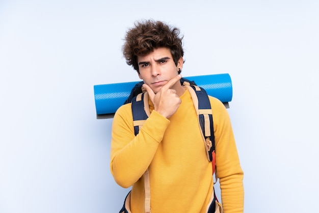Jeune homme alpiniste avec un gros sac à dos sur le mur bleu isolé en pensant à une idée