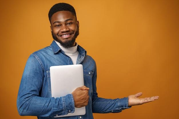 Jeune, homme américain africain, debout, à, ordinateur portable, contre