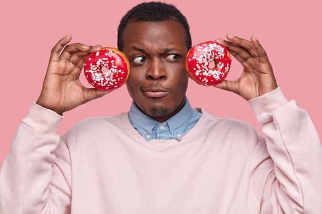 Jeune, homme américain africain, tenue, savoureux, beignets