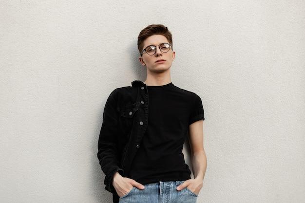 Un jeune homme américain moderne dans des lunettes à la mode dans des vêtements en denim décontractés élégants en t-shirt noir repose près du bâtiment à l'extérieur. mannequin urbain cool guy en ville. style de rue des jeunes.