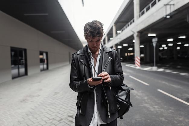 Jeune homme américain en veste de cuir noir avec sac à dos avec coiffure avec téléphone portable moderne se trouve dans la ville. beau mec hipster dans des vêtements à la mode se dresse et regarde le smartphone à l'extérieur.