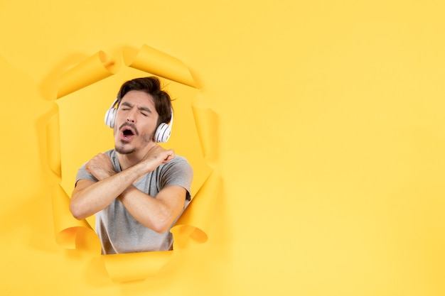 Jeune homme amusé dans les écouteurs sur fond de papier jaune déchiré son audio ultrasonore
