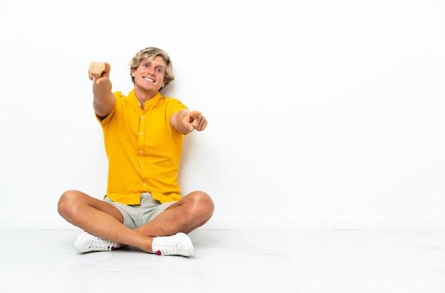 Jeune homme anglais assis sur le sol pointant vers l'avant avec une expression heureuse