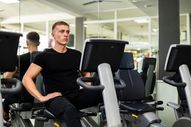 Jeune homme à l'angle élevé à la pratique de la gym