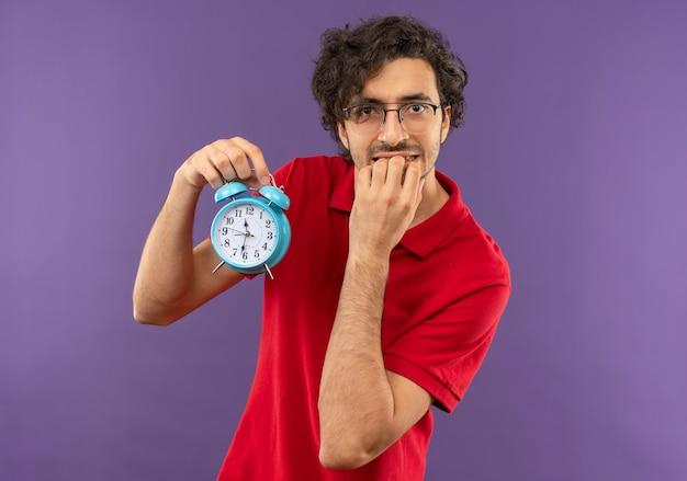 Jeune homme anxieux en chemise rouge avec des lunettes optiques détient horloge et met la main sur la bouche isolé sur mur violet