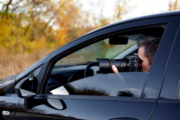 Jeune homme avec un appareil photo reflex numérique dans une voiture