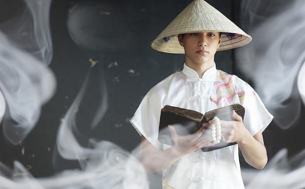 Le jeune homme d'apparence asiatique dans un kimono prie avec un livre