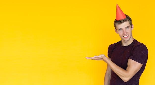 Jeune homme d'apparence européenne sur fond jaune. concept d'anniversaire avec casquette sur la tête, pointe avec la main vers un espace vide pour le texte