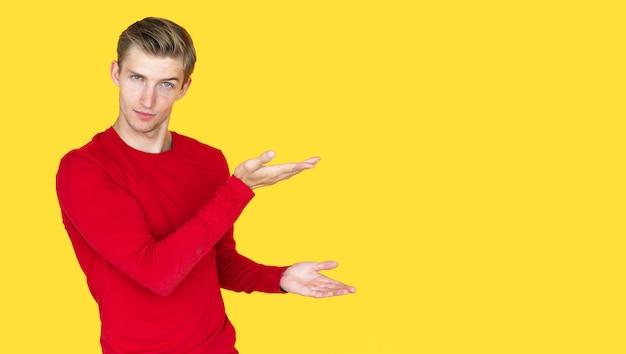 Jeune homme d'apparence européenne sur fond jaune. avec deux paumes ouvertes indique un espace vide pour le texte