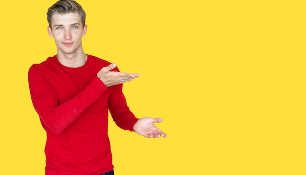 Jeune homme d'apparence européenne sur fond jaune. dirige les deux mains vers un espace vide. espace de copie