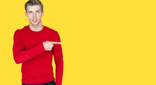 Jeune homme d'apparence européenne sur fond jaune. dirige l'index de la main vers un endroit vide. espace de copie
