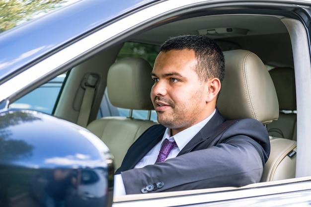 Un jeune homme d'apparence moyen-orientale en costume d'affaires conduit une voiture chère.