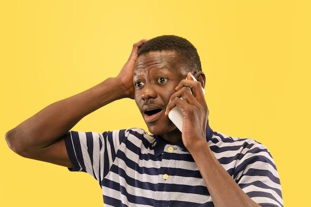 Jeune homme appelant isolé sur mur de studio jaune