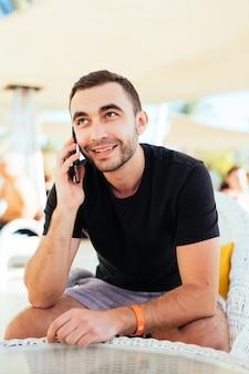 Jeune homme appelant par téléphone portable dans un café en plein air sur la station balnéaire à la plage