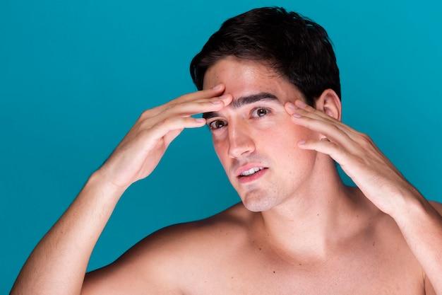 Jeune homme appliquant des soins de la peau