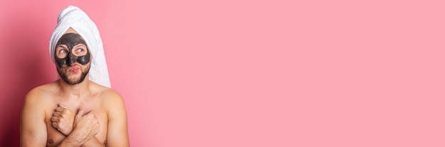 Le jeune homme applique un masque facial hydratant, regarde pensivement sur le côté sur un fond rose.