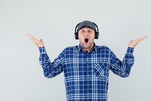 Jeune homme appréciant la musique avec des écouteurs en chemise, casquette et à la surprise. vue de face.