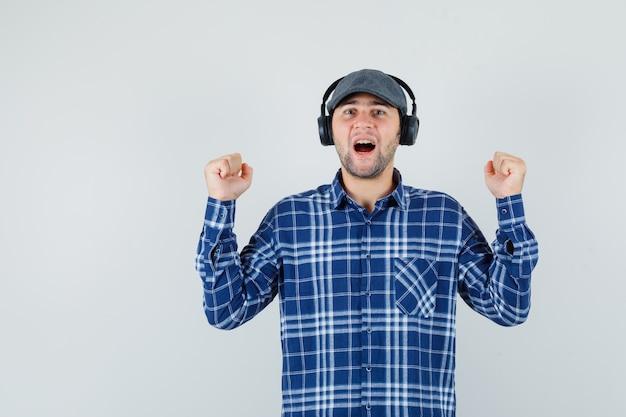 Jeune homme appréciant la musique avec des écouteurs en chemise, casquette et à la vue de face, heureux.