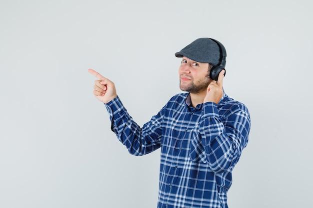 Jeune homme appréciant la musique avec des écouteurs, pointant vers l'extérieur en chemise, casquette, vue de face.