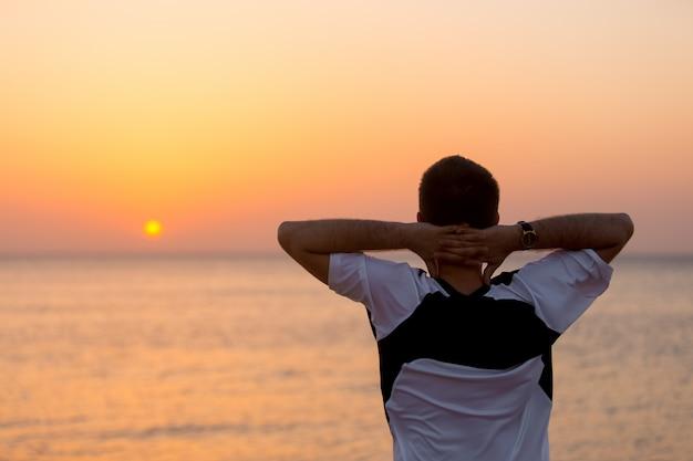 Jeune homme apprécie la vue sur la mer