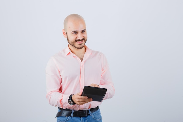 Jeune homme appuyant sur les boutons de la calculatrice en chemise rose, jeans et à l'optimisme. vue de face.
