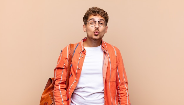 Jeune homme en appuyant sur les lèvres avec une expression mignonne, amusante, heureuse et charmante, envoyant un baiser. concept étudiant
