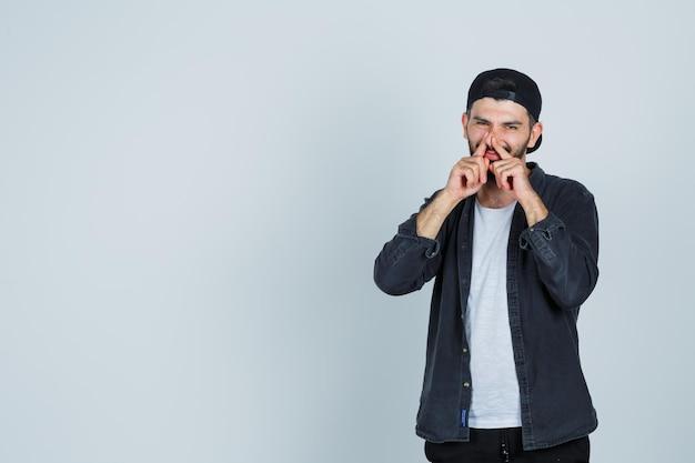 Jeune homme en appuyant sur le nez avec les doigts