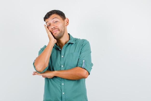 Jeune homme appuyé sur la joue sur la paume surélevée en chemise et à la joyeuse