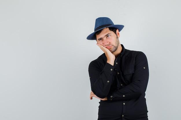 Jeune homme appuyé sur la joue sur la paume surélevée en chemise noire