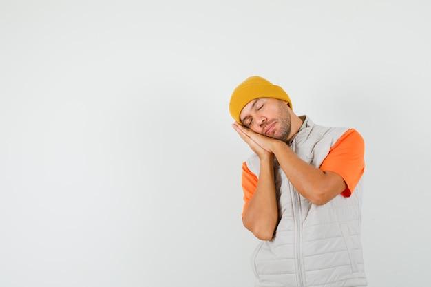 Jeune homme appuyé sur les paumes comme oreiller en t-shirt, veste, chapeau et à la détente. vue de face.