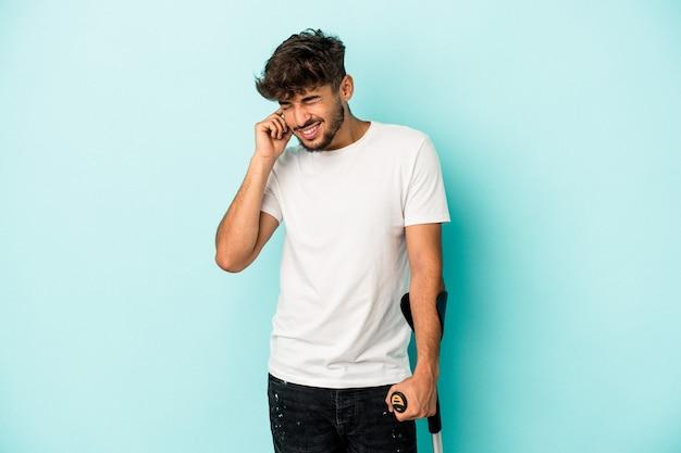 Jeune homme arabe avec des béquilles isolé sur fond bleu couvrant les oreilles avec les mains.
