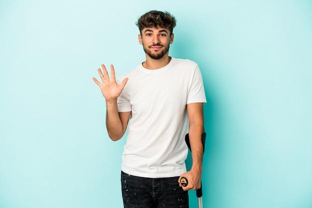 Jeune homme arabe avec des béquilles isolé sur fond bleu souriant joyeux montrant le numéro cinq avec les doigts.